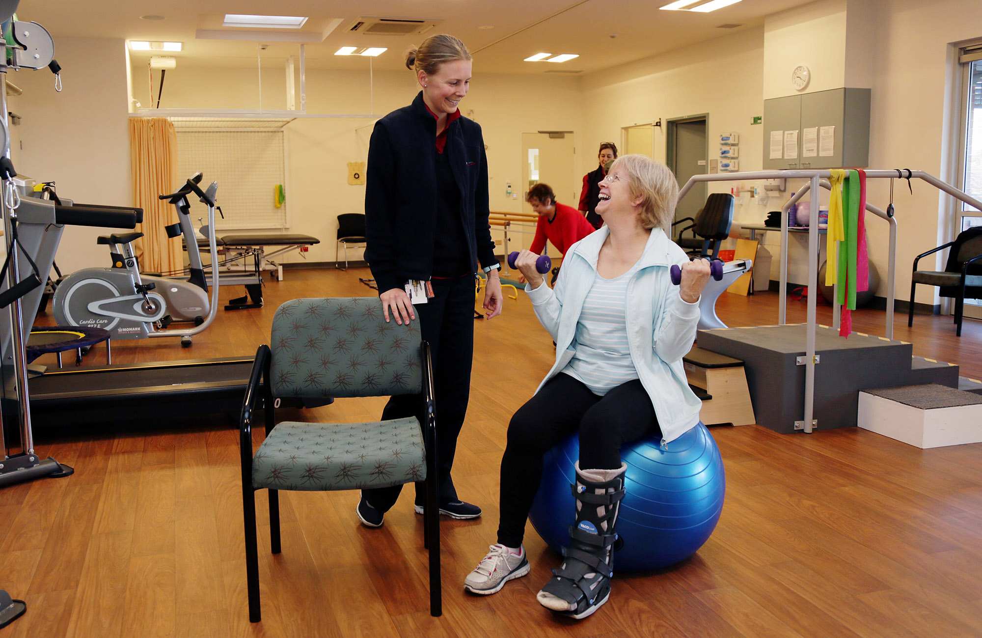 Exercise Physiologist supports a patient in the her rehabilitation. Patient seated on an exercise ball using hand weights.